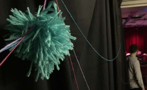 A fluffy handmade cancer cell attached to the threads of clinical trials stories disappearing into the theatre
